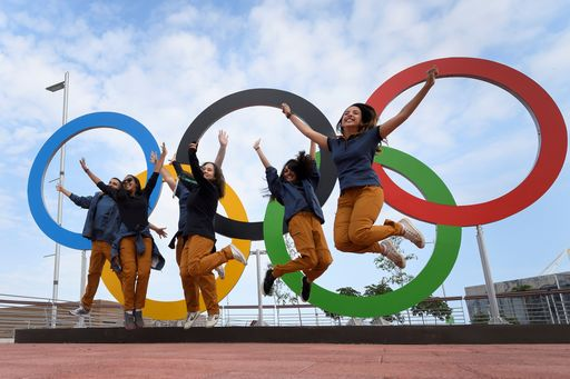 TOPSHOT - People jump for a picture in front of Olympic Rings set at the Olympic parc in Rio de Janeiro on August 3, 2016, ahead of the Rio 2016 Olympic Games. / AFP PHOTO / FABRICE COFFRINI