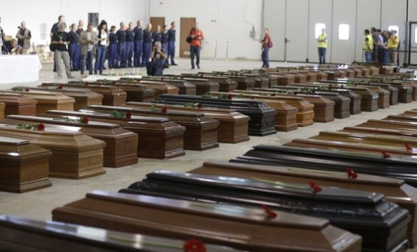 Coffins of died migrants are lined up inside an hangar of Lampedusa's airport, Italy, Saturday, Oct. 5, 2013. A ship carrying African migrants towards Italy capsized Thursday off the Sicilian island of Lampedusa after the migrants on board started a fire to attract attention. Just 155 people survived, 111 bodies have been recovered and more than 200 are still missing. The tragedy has prompted outpourings of grief and calls for a comprehensive EU immigration policy to deal with the tens of thousands fleeing poverty and strife in Africa and the Middle East. (AP Photo/Luca Bruno)