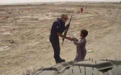 Un carabiniere lascia una bottiglia d'acqua ad un bimbo